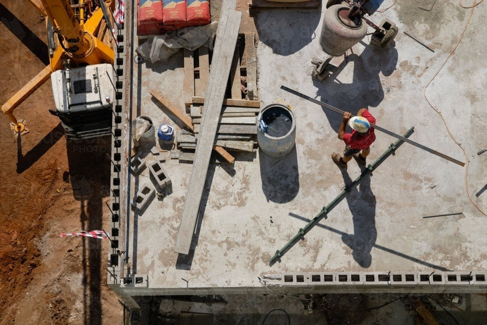 An overhead view of a construction worker carrying a beam on a building site - Australian Stock Image