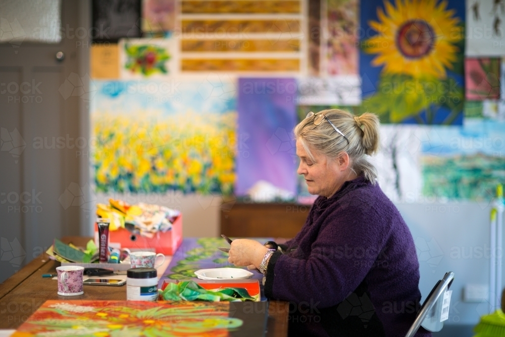 Artist working in colourful studio - Australian Stock Image