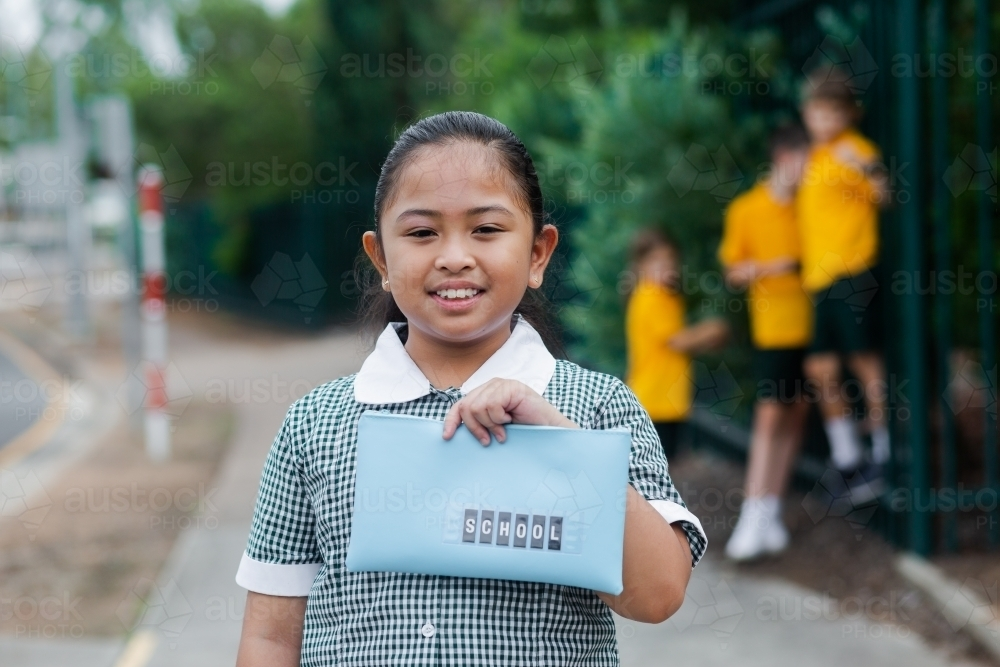 Aussie kid of Filipino ethnicity holding out a pencil case ready for going back to school - Australian Stock Image