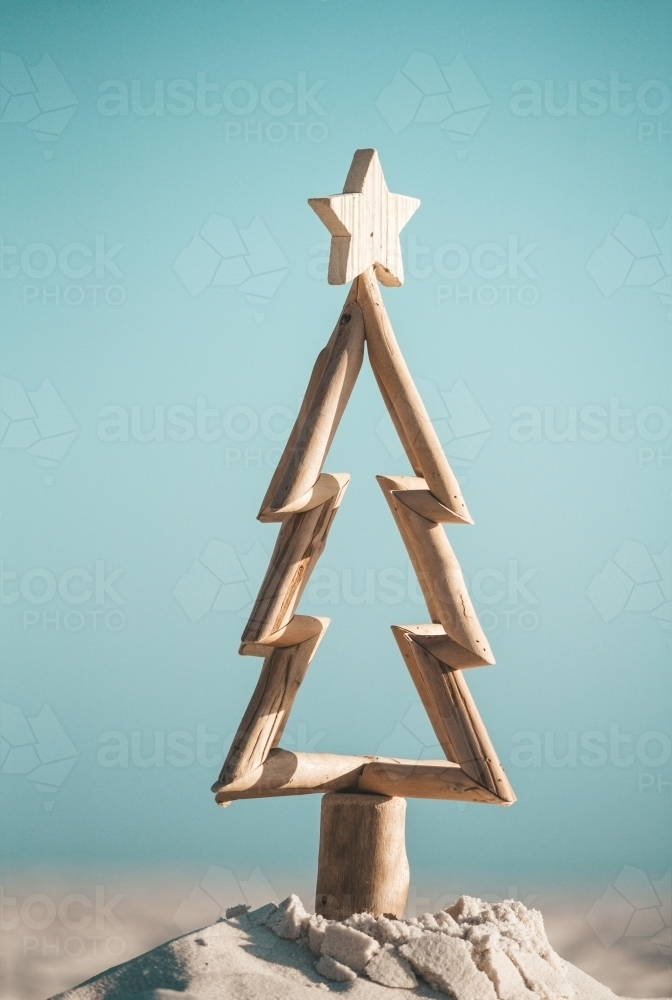 Australian Christmas.  Driftwood timber Christmas tree in sand by the ocean - Australian Stock Image