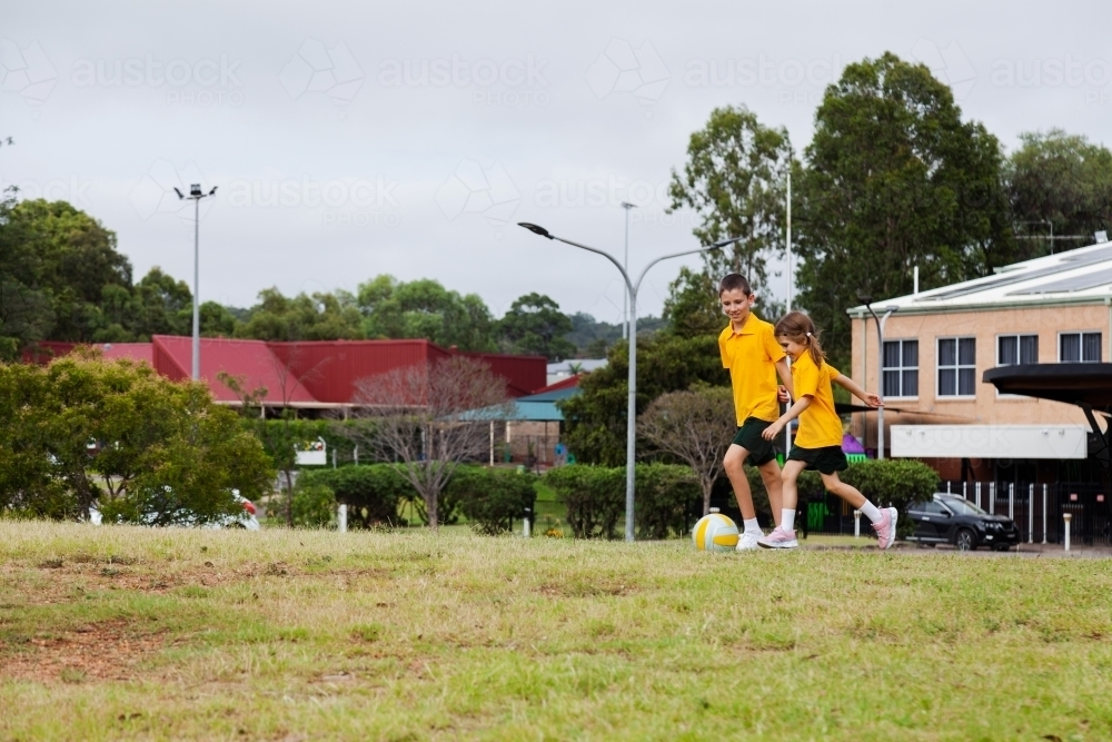 Australian primary school students running after a ball - Australian Stock Image