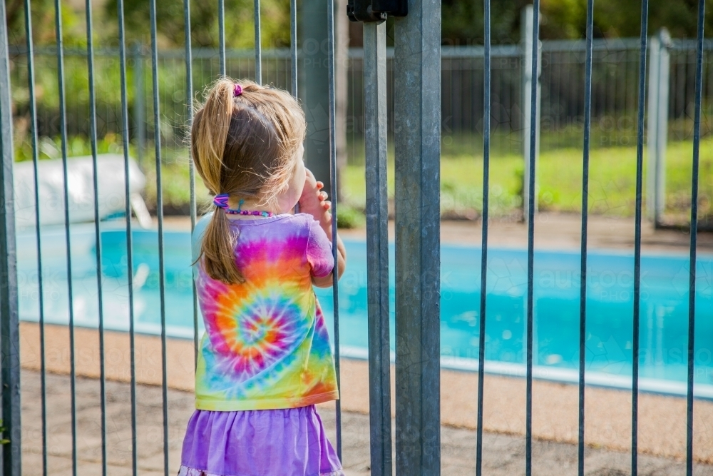 Little Girl Standing Safely Outside Pool Fence Gate Looking In