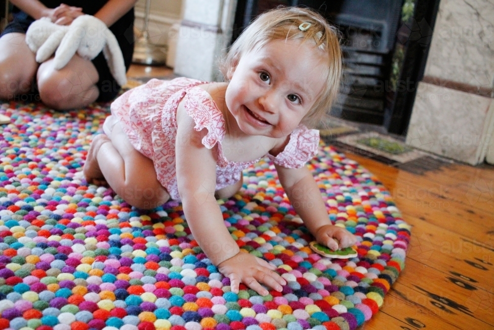 Baby girl crawling on a rug - Australian Stock Image