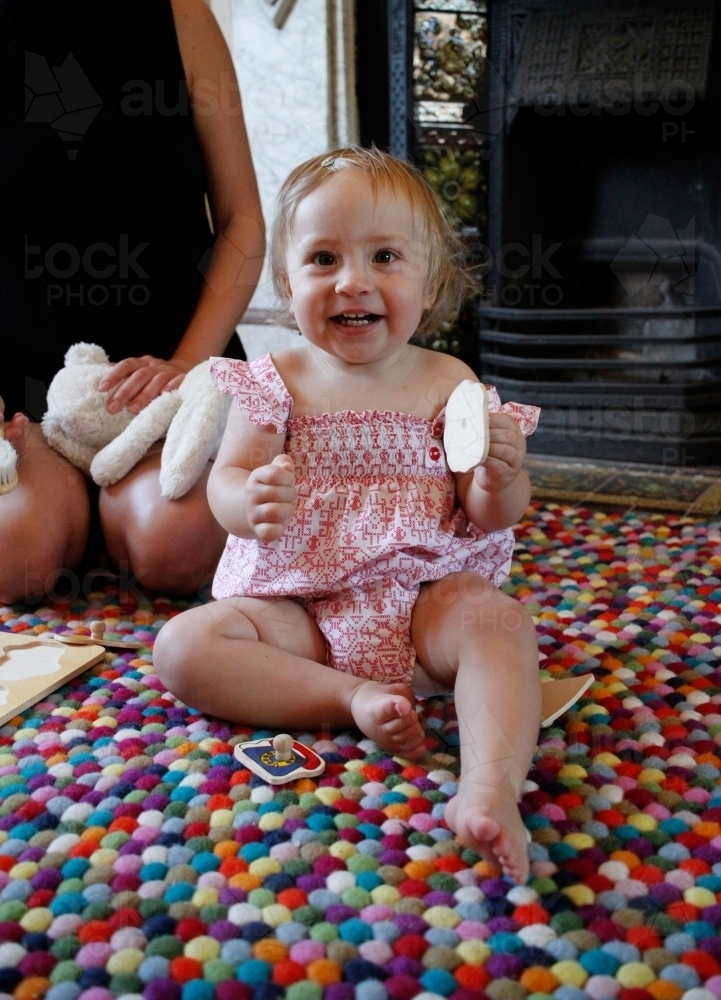 Baby girl sitting on a rug, playing with toys and smiling at camera. - Australian Stock Image