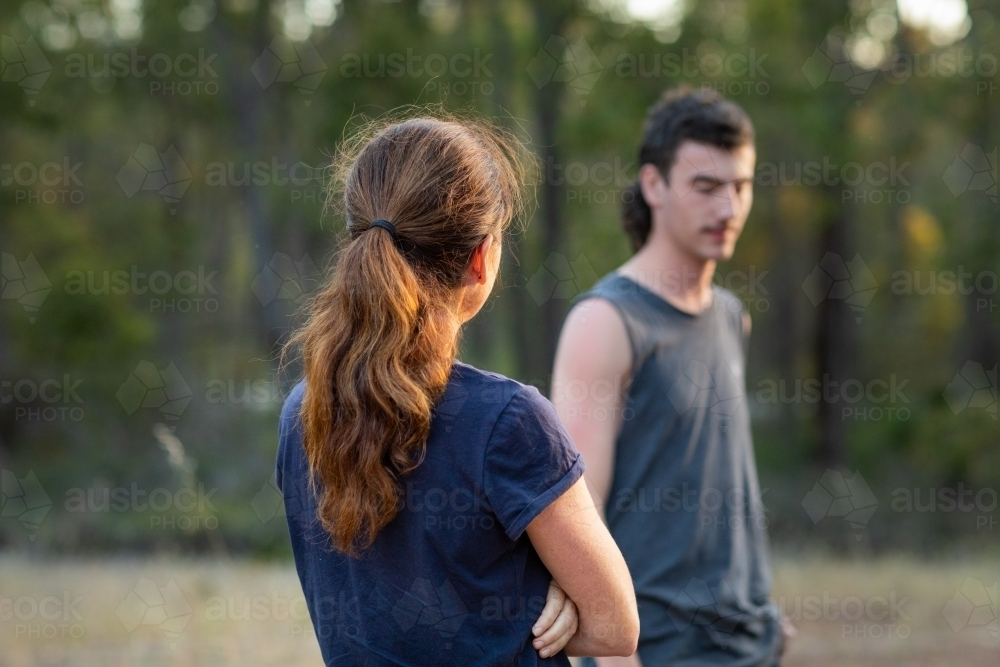 back of woman's head as she looks at her teenage son - Australian Stock Image