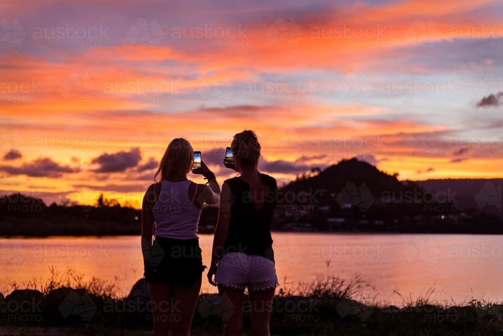 Backpackers photographing a brilliant sunset on their phones. - Australian Stock Image