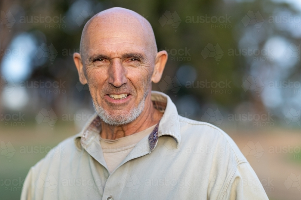 bald man outdoors with blurred bush background - Australian Stock Image