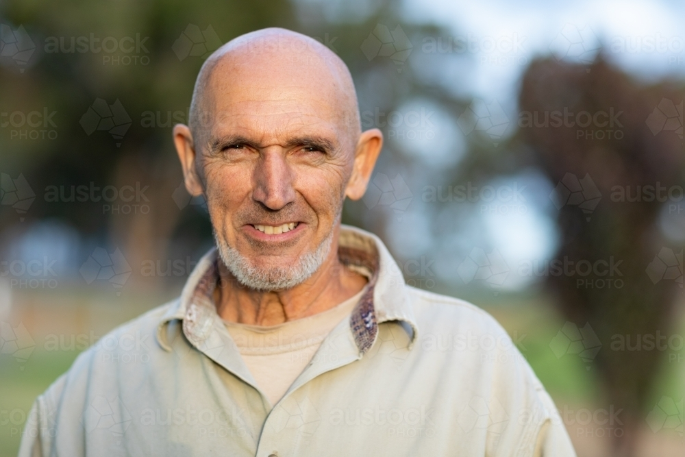 bald mature man head and shoulders smiling and looking at camera - Australian Stock Image