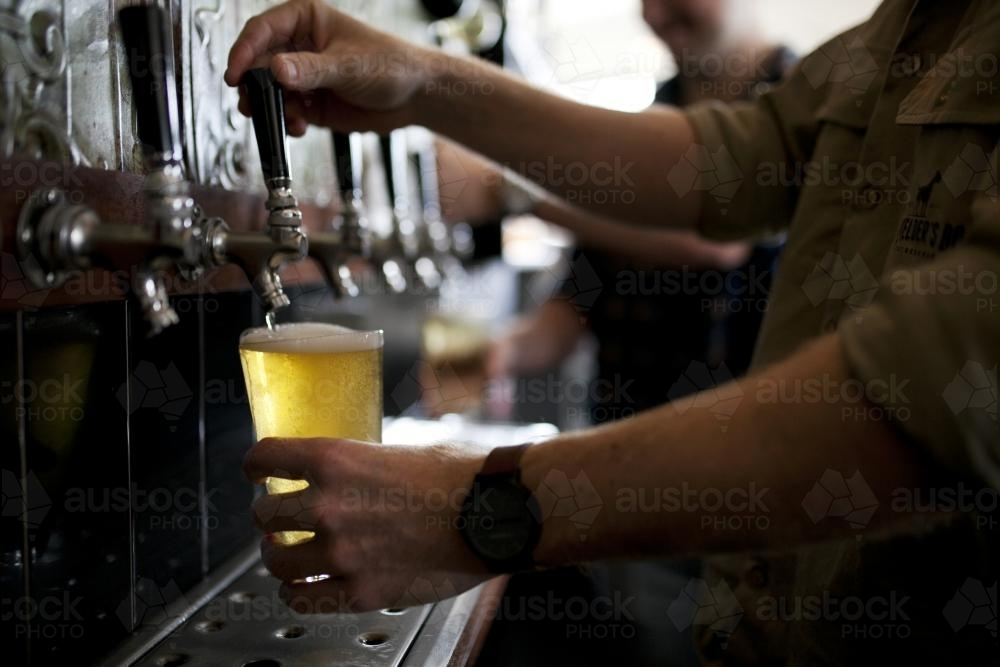 Bartenders pouring drinks from tap at local craft beer bar - Australian Stock Image