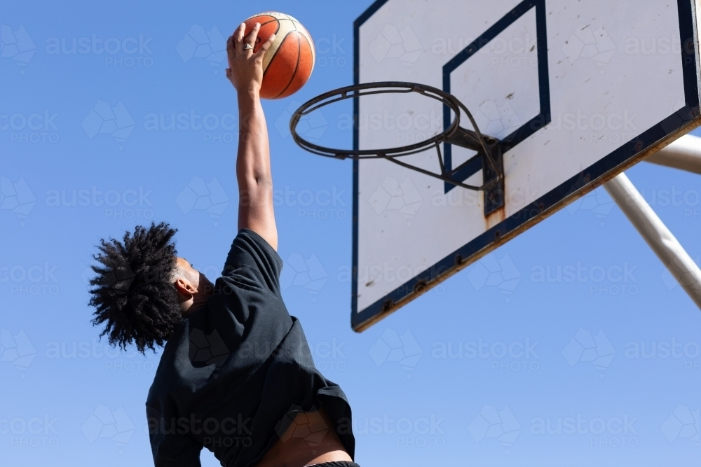 Basketball hoop with young guy about to slam a goal - Australian Stock Image