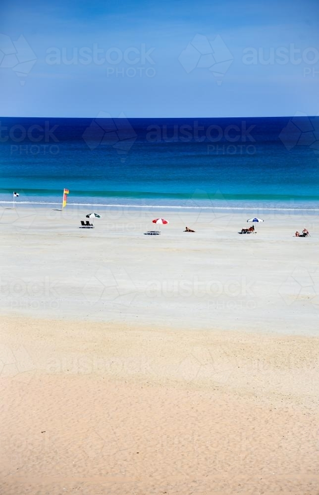 Beach scene with beach umbrellas and blue water - Australian Stock Image