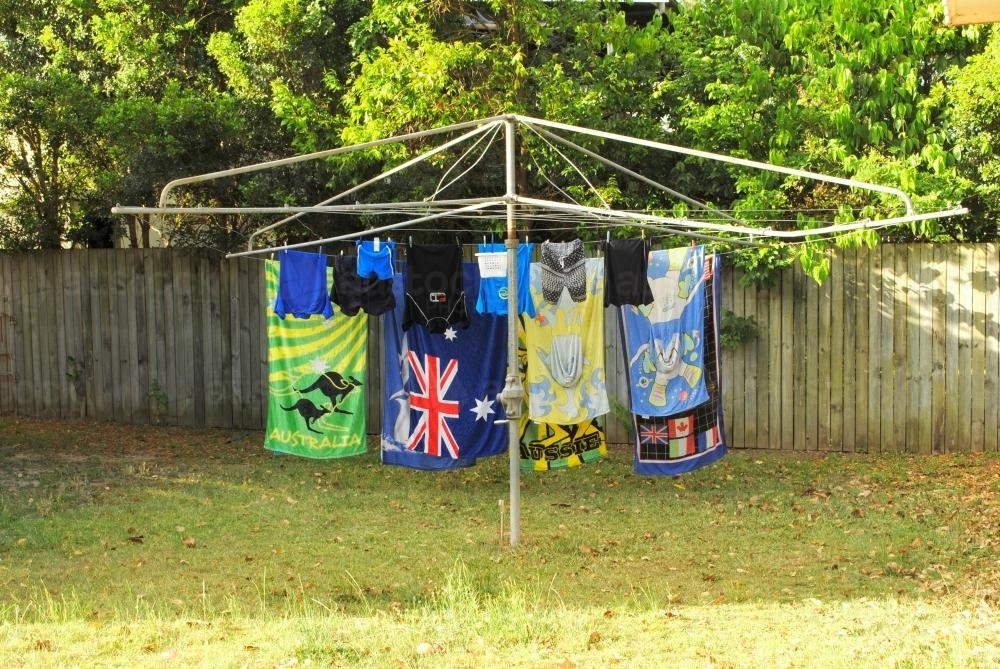 Beach towels and swimwear are hanging on a Hills Hoist in a suburban garden - Australian Stock Image