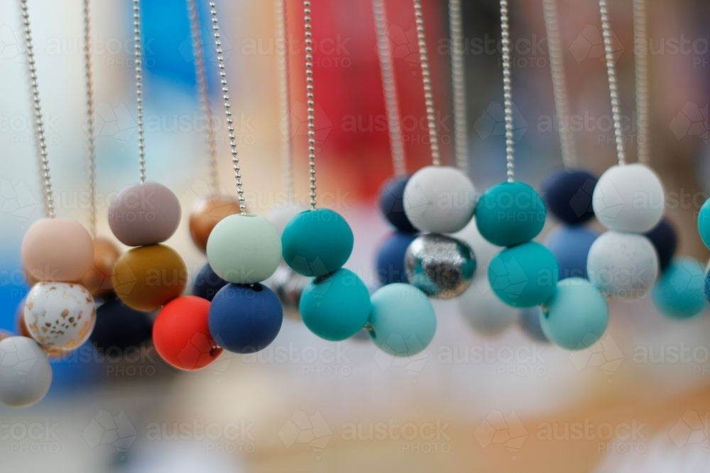Beaded necklaces hanging at a market stall - Australian Stock Image