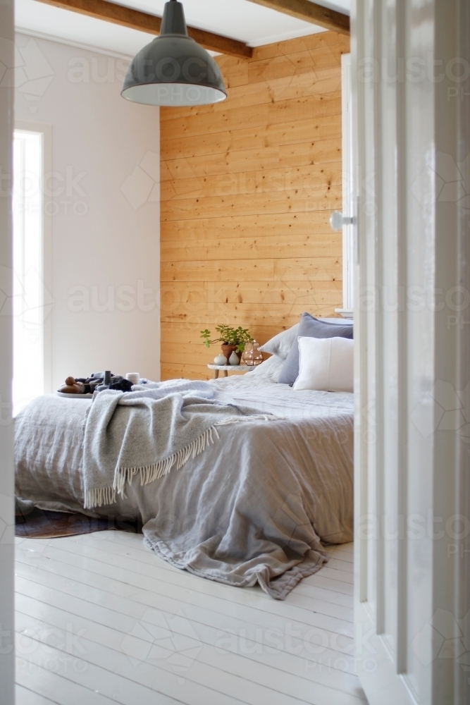 Bedroom through doorway with grey linen on bed and coffee table - Australian Stock Image