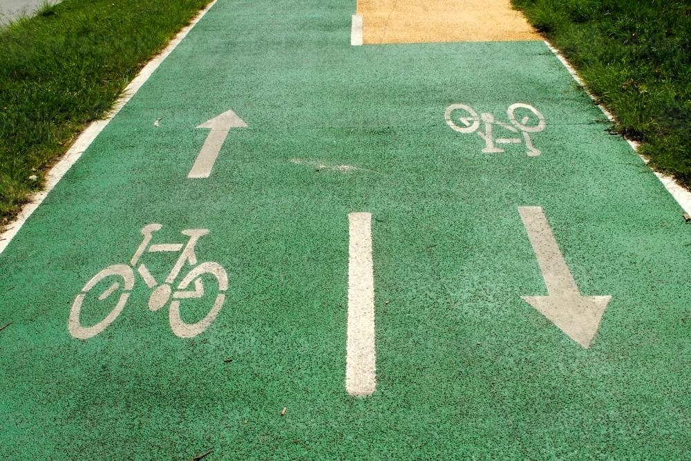Bicycle and arrow signs painted in white on green asphalt - Australian Stock Image