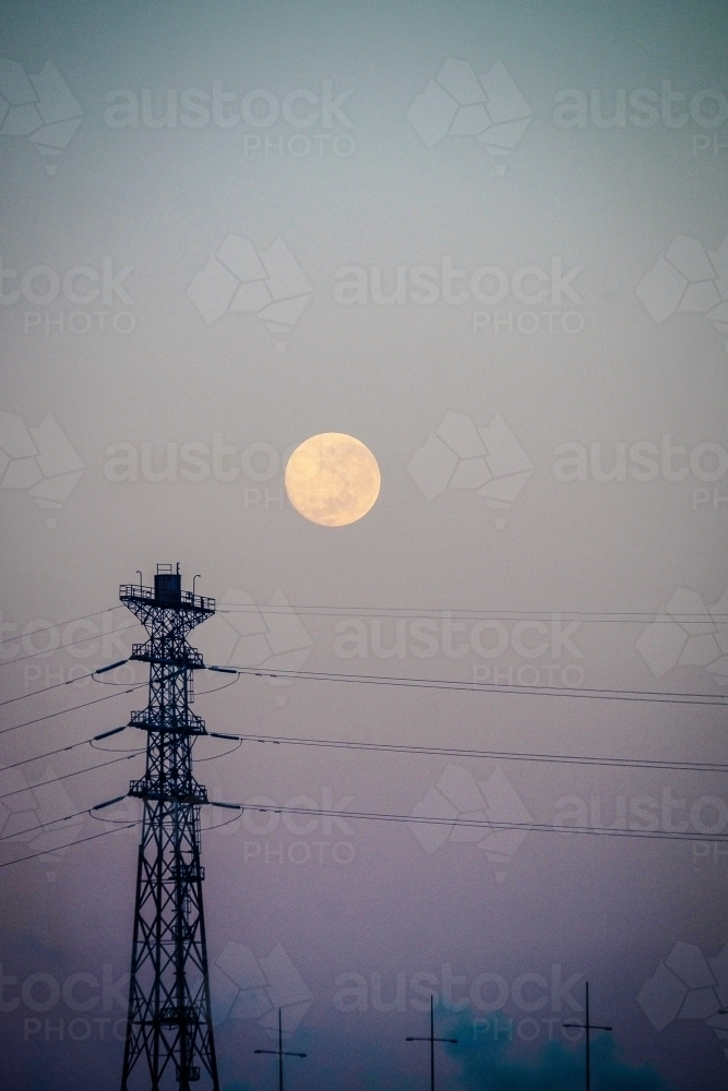 Big moon and a city sky with power lines. - Australian Stock Image
