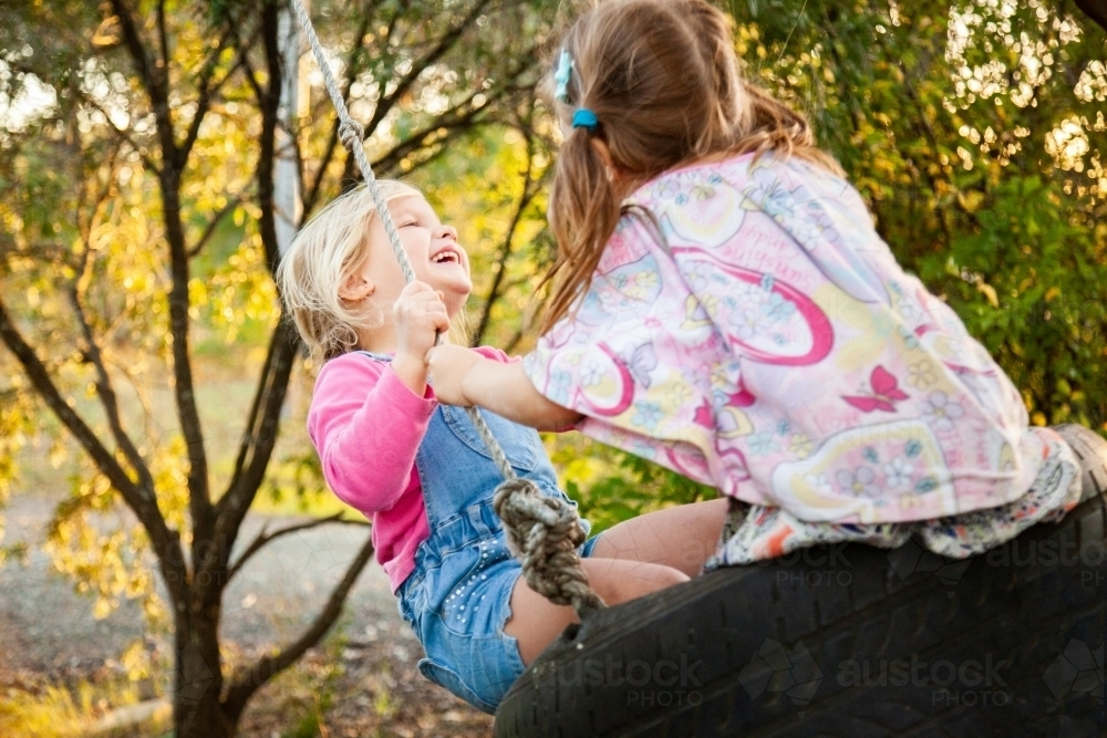 Blond and brunette little girls laughing on swing together - Australian Stock Image