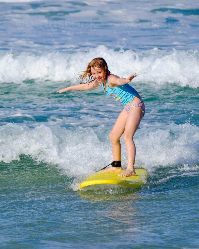Blonde girl surfing off South Stradbroke Island on the Gold Coast - Australian Stock Image