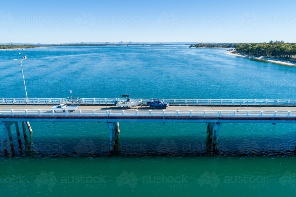 Blue ute towing a fishing boat on bridge over water. - Australian Stock Image