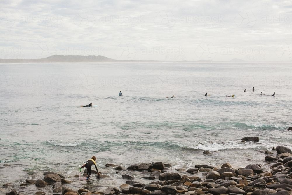 Board Surfers shown from rock outcrop - Australian Stock Image