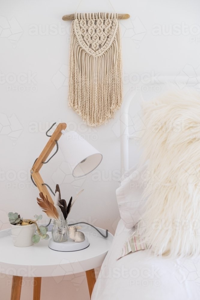 Bohemian style bed with side table and macrame - Australian Stock Image