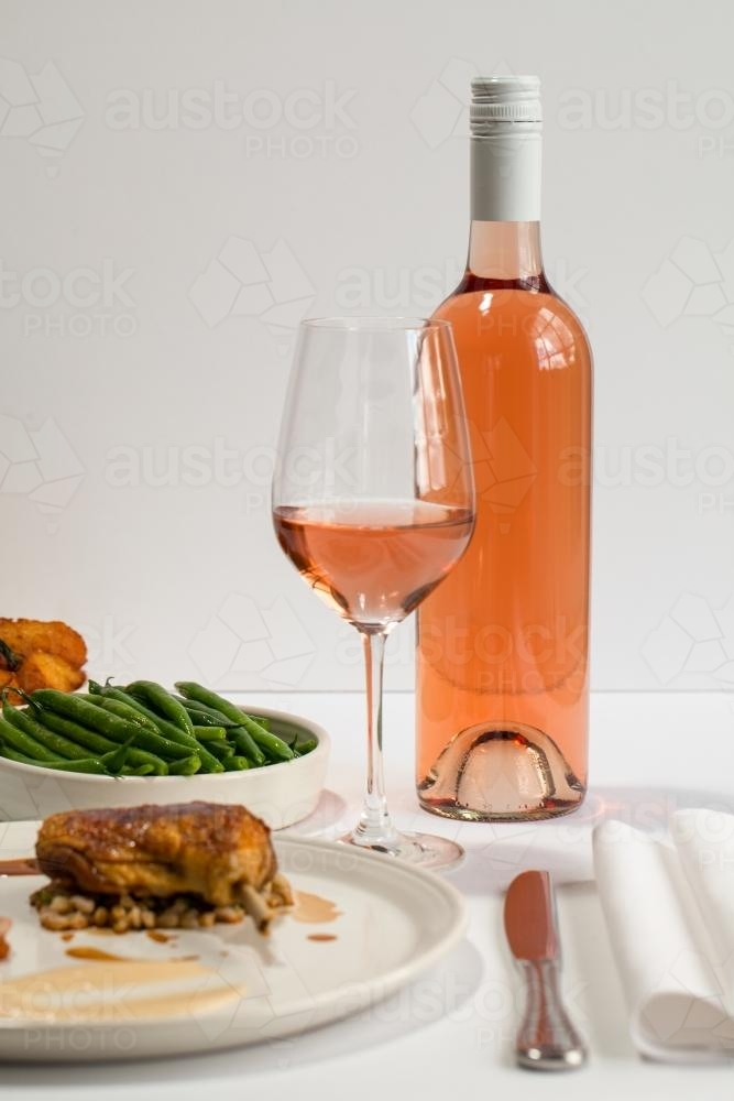 Bottle of rose wine with roast duck and vegetable plate - Australian Stock Image