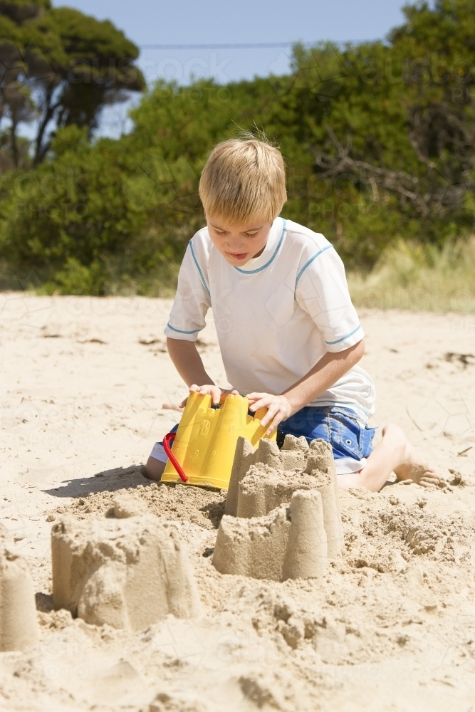 Boy building sand castle at the beach - Australian Stock Image