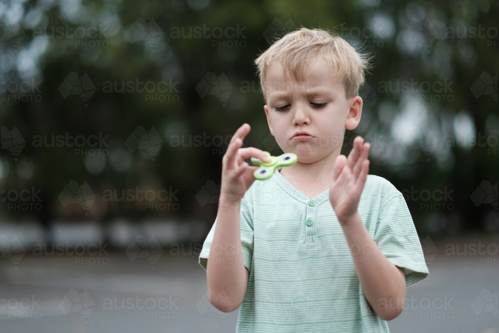Boy frowning playing with fidget spinner toy - Australian Stock Image