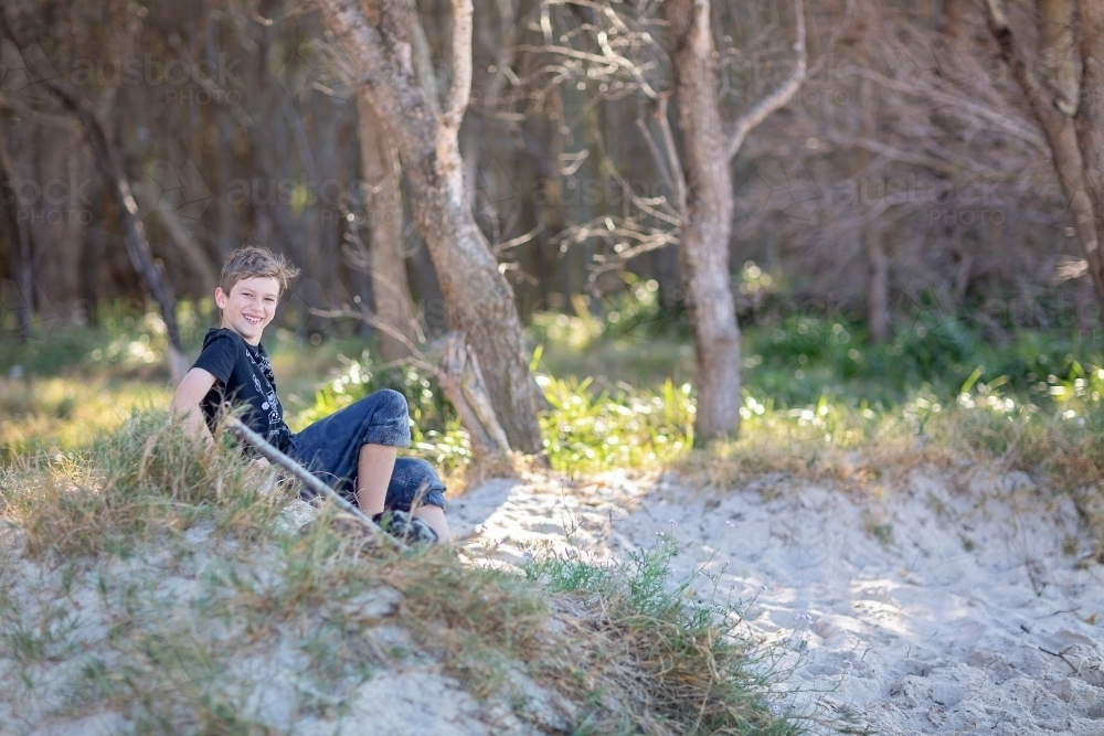 Boy having fun on the sand dunes on a remote beach in Queensand - Australian Stock Image