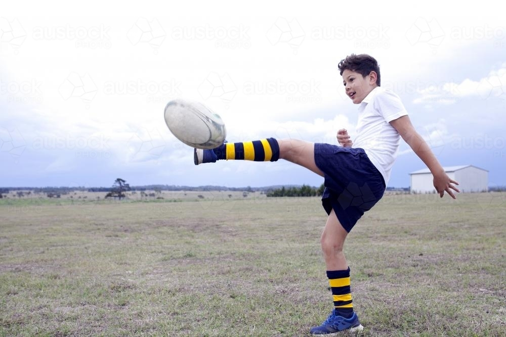 image of boy kicking a rugby football in a field austockphoto