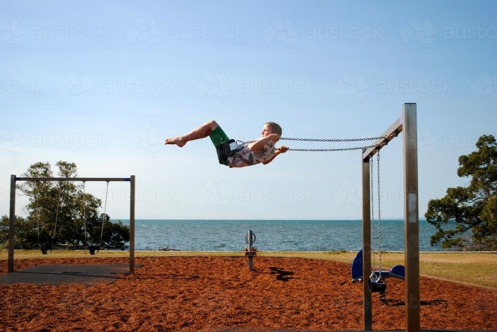 Boy on a swing in a playground near the sea - Australian Stock Image