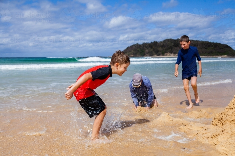 Boy splashing in water at the beach beside sand castle - Australian Stock Image