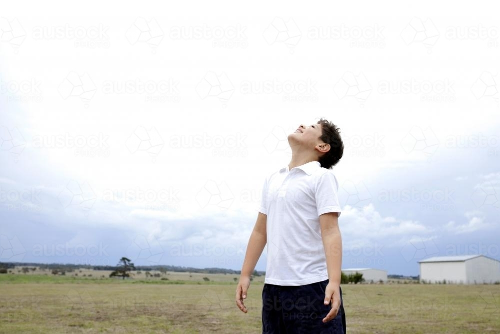 Boy standing in open field looking up at sky - Australian Stock Image