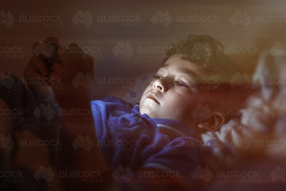 Boy using smart phone in dark bedroom - Australian Stock Image