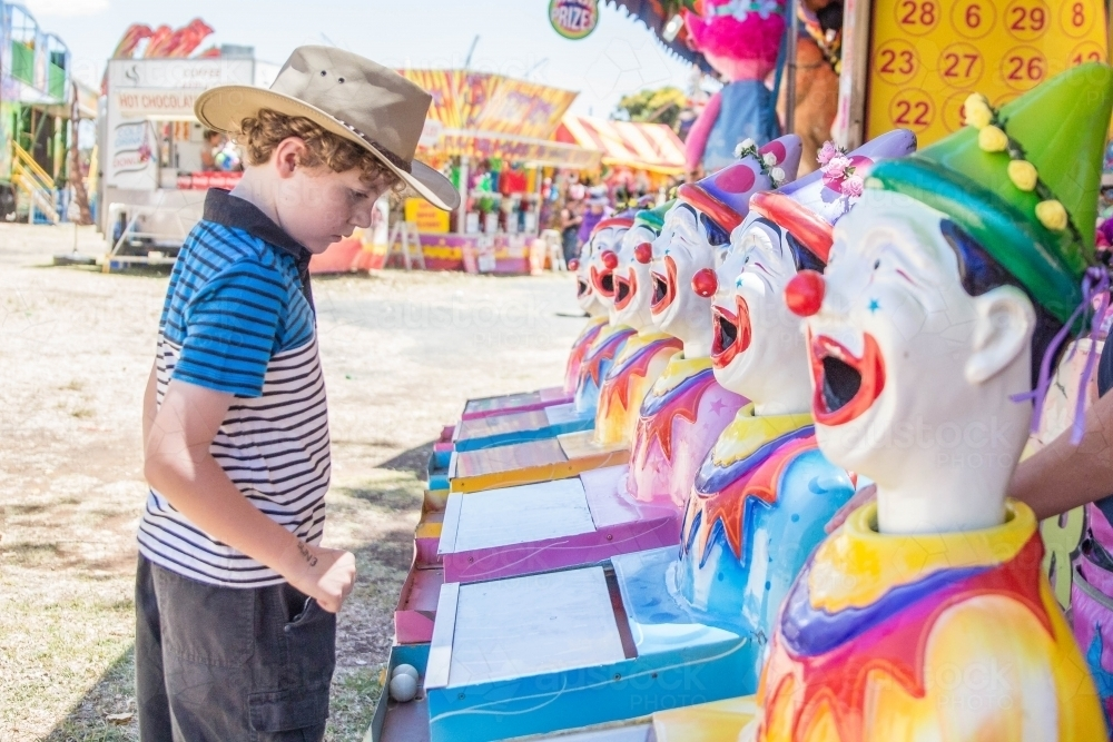 Boy wearing akubra hat playing clown sideshow alley at local show - Australian Stock Image