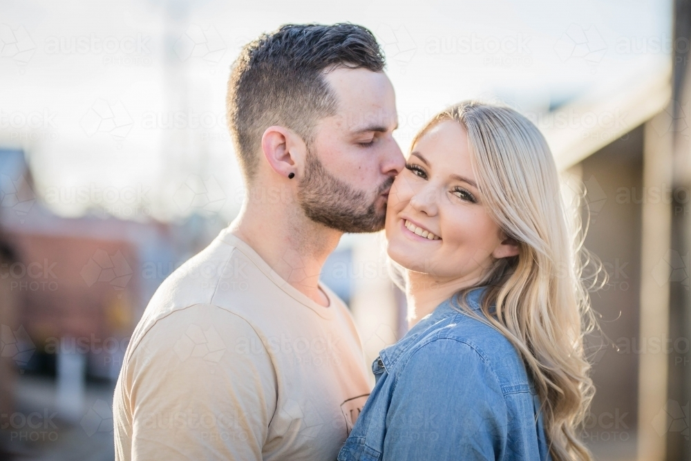 Image of Boyfriend kissing smiling girlfriend on cheek