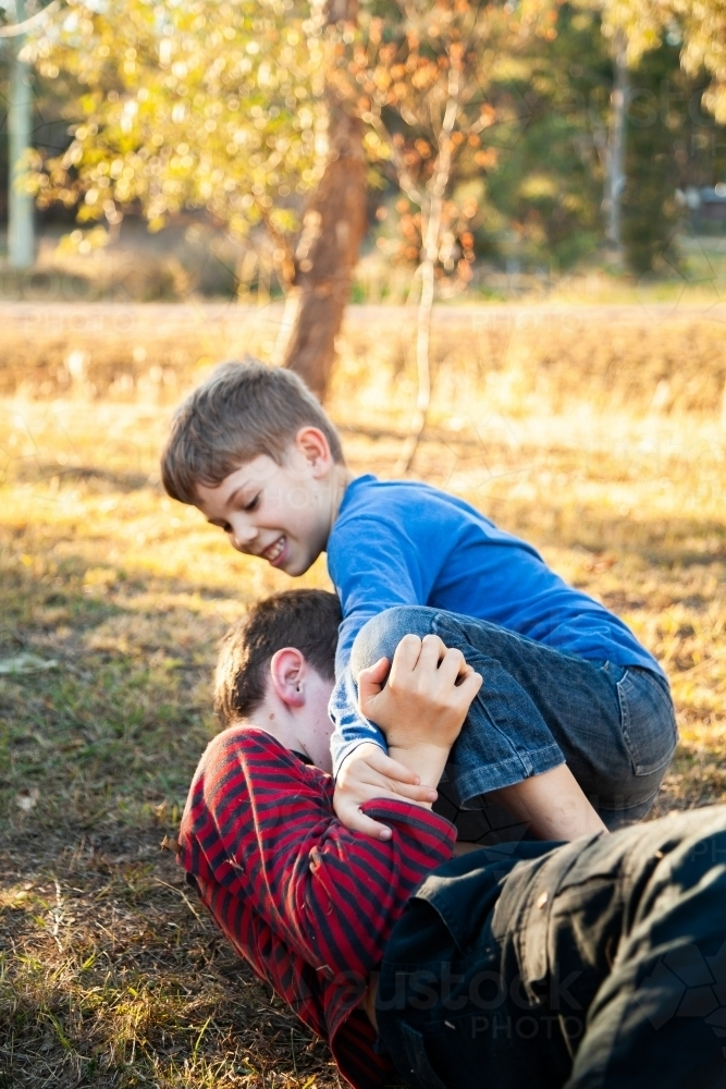 Brothers tackle wrestling each other outside - Australian Stock Image