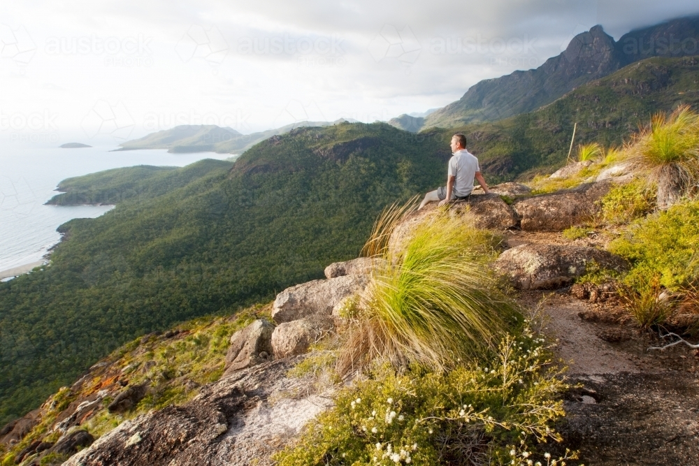 Bushwalker looking away from camera at view over coastline - Australian Stock Image
