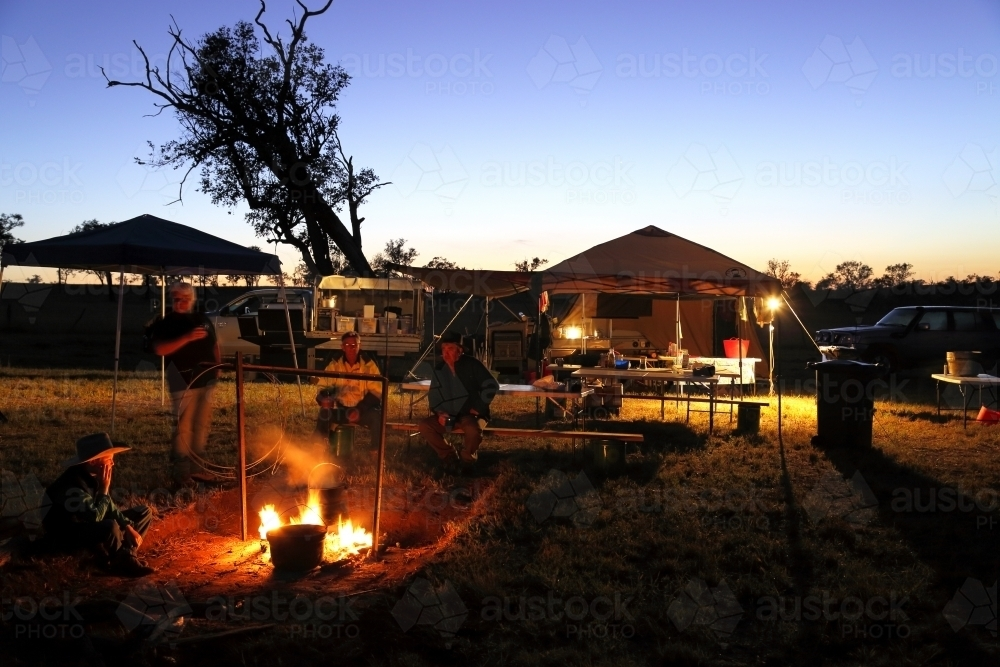 Campers gathered around a campfire - Australian Stock Image