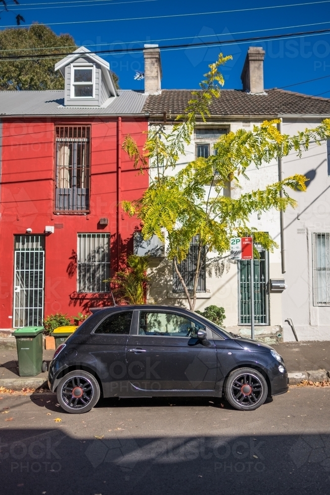 Car parked in front of colourful terrace houses in Sydney suburb - Australian Stock Image