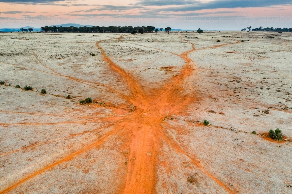 Cattle tracks in red dirt leading through a gateway - Australian Stock Image