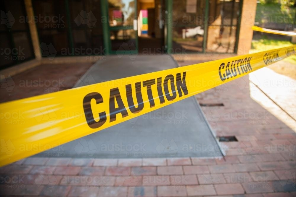 Caution tape stopping people walking on wet concrete ramp - Australian Stock Image