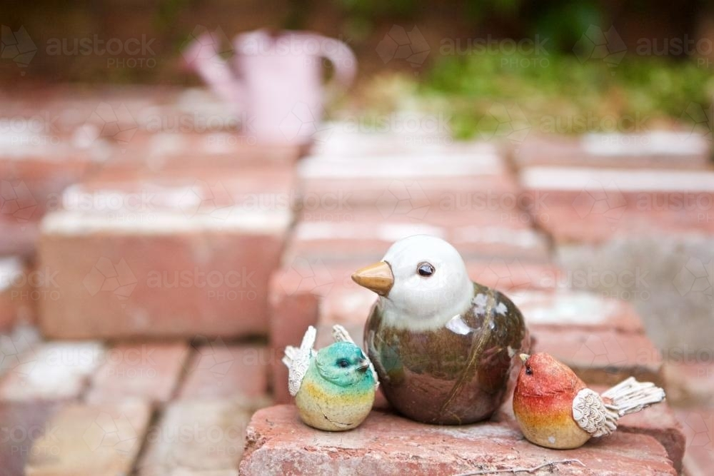 Ceramic bird statuettes of birds sittings on a pile of bricks - Australian Stock Image