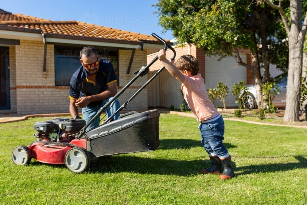 child trying to push lawnmower watched by father - Australian Stock Image