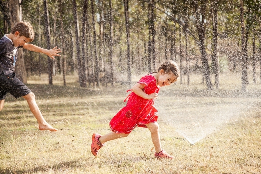 Children running under sprinkler in backyard, Aussie summer childhood - Australian Stock Image