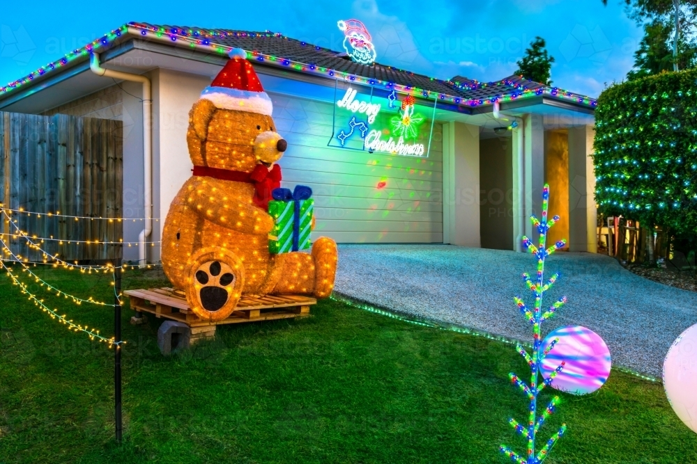 Christmas decorations in Queensland with a large teddy bear in front - Australian Stock Image
