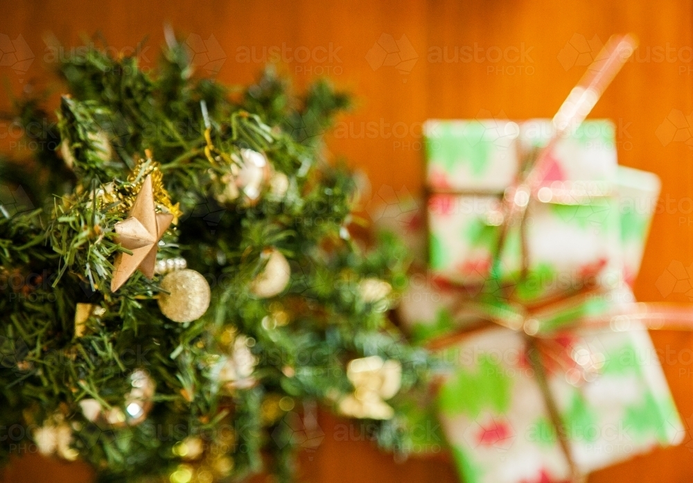 Christmas gifts under a small decorated tree with a star on top - Australian Stock Image