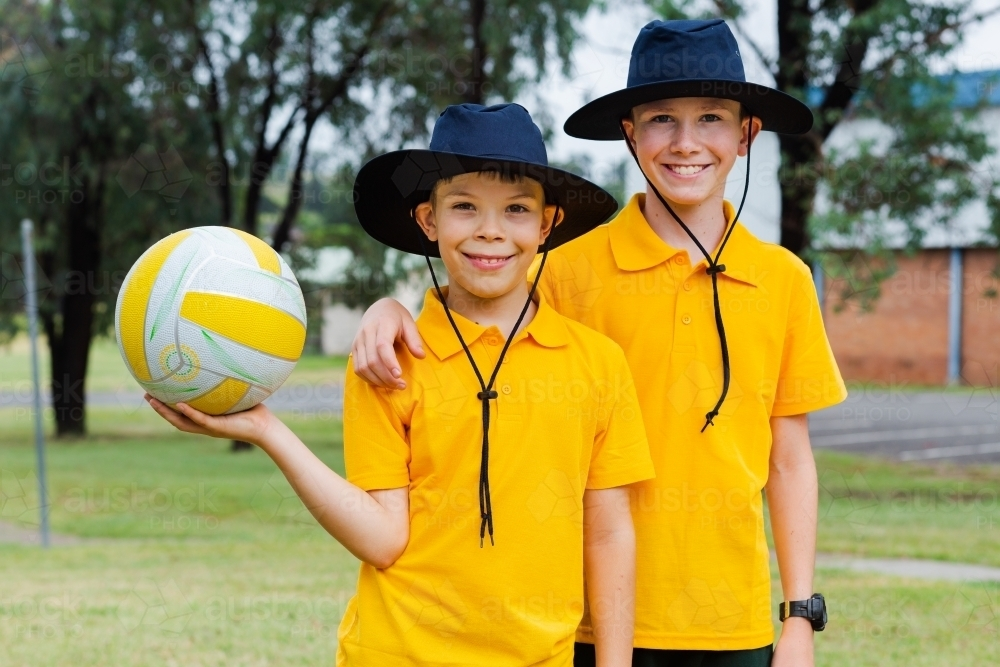 Classmates standing outside in the playground with hats on and a ball - Australian Stock Image