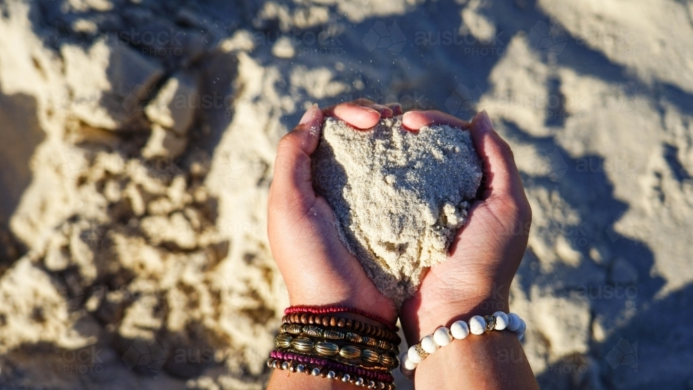 Close of hands holding sand in heart shape - Australian Stock Image