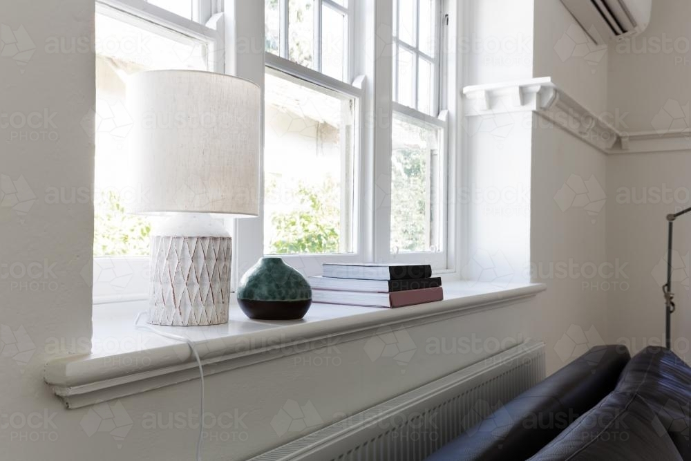 Close up details of lamp books and ornament objects on windowsill - Australian Stock Image